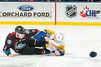 KELOWNA, CANADA - DECEMBER 1:  Dalton Gally #3 of the Kelowna Rockets and Riley McKay #39 of the Saskatoon Blades drop to the ice after dropping the gloves on December 1, 2018 at Prospera Place in Kelowna, British Columbia, Canada.  (Photo by Marissa Baecker/Shoot the Breeze)