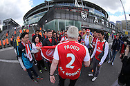 """an Arsenal fan wearing """"Proud 2 be a gooner"""" shirt talks to fans from Hong Kong outside the Emirates Stadium before k/o . Barclays Premier league match, Arsenal v Crystal Palace at the Emirates Stadium in London on Sunday 17th April 2016.<br /> pic by John Patrick Fletcher, Andrew Orchard sports photography."""