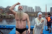 Moscow, Russia, 18/01/2007.Two Orthodox believers make the sign of the cross while celebrating Epiphany at Serebryany Bor in northern Moscow. Normally all rivers and lakes are frozen at this time of year, and the ceremony takes place on the frozen lake, with the believers being baptised in holes in the ice. However Moscow is experiencing its warmest winter ever, with the temperature plus 3 Celsius today, in contrast to minus 30 during last year's holiday.