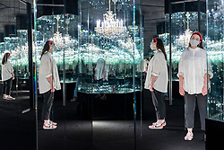 """© Licensed to London News Pictures. 17/05/2021. LONDON, UK. A Tate staff member views """"Chandelier of Grief"""", 2016, by Yayoi Kusama. Preview of Yayoi Kusama: Infinity Mirror Rooms on show at Tate Modern, in partnership with Bank of America with additional support from UNIQLO, from 18 May to 12 June 2022.  Photo credit: Stephen Chung/LNP"""