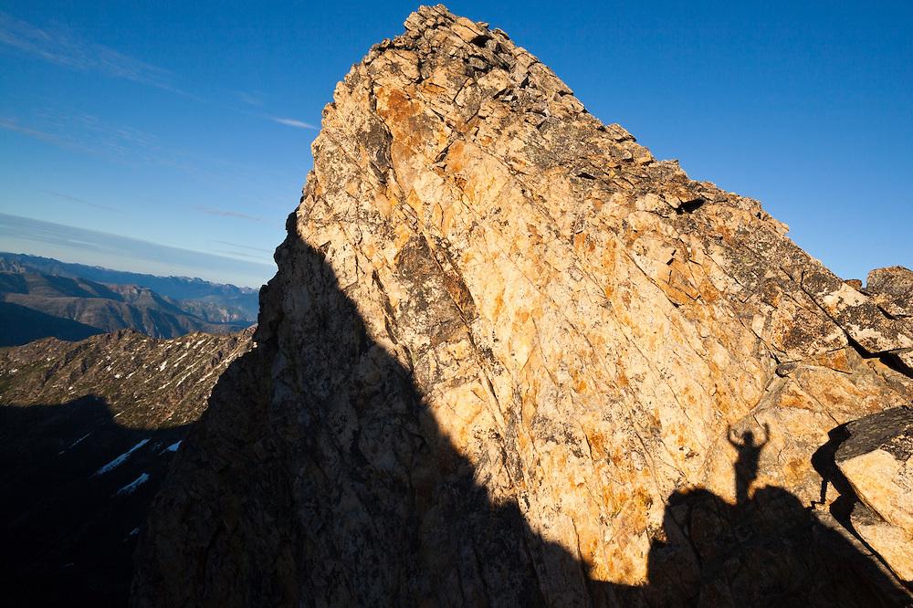 A hiker's shadow projected onto a rock buttress, celebrates on a climb of Golden Horn, Okanogan National Forest, Washington.
