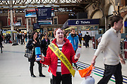 """A woman wearing a yellow sash """"Helping the Homeless"""" is collecting money donations for a homeless charity from members of the public passing through London Victoria railway station. The train station is located in central London and is the second-busiest in the capital."""