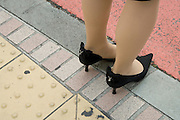 woman in stylish shoes waiting to cross the road