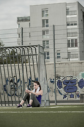 Young woman checking test results on mobile phone and sitting on football ground, Bavaria, Germany