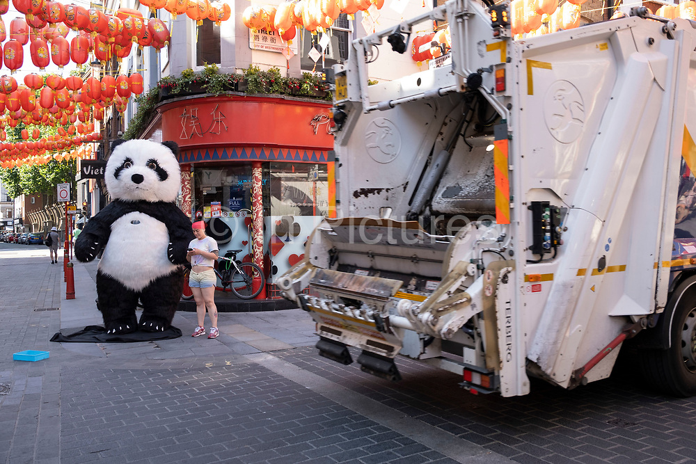 Rubbish truck passes some people trying to earn some money from tourists dressed up as a Giant Panda on the corner of Gerrard Street in Chinatown which remains very quiet with a few people visiting Chinese restaurants to pick up food and to see the red lanterns on 26th June 2020 in London, England, United Kingdom. As the July deadline approaces and government will relax its lockdown rules further, the West End remains quiet, while some non-essential shops are allowed to open with individual shops setting up social distancing systems.