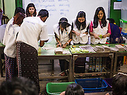 08 NOVEMBER 2015 - YANGON, MYANMAR:  Elections workers count the votes at a polling place in Yangon. Elections workers counted the ballots at each polling place then called the results into the national elections office. It could be more than one week before the official results are completely tabulated. The citizens of Myanmar went to the polls Sunday to vote in the most democratic elections since 1990. The National League for Democracy, (NLD) the party of Aung San Suu Kyi is widely expected to get the most votes in the election, but it is not certain if they will get enough votes to secure an outright victory. The polls opened at 6AM. In Yangon, some voters started lining up at 4AM and lines were reported to long in many polling stations in Myanmar's largest city.    PHOTO BY JACK KURTZ