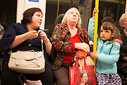 Three generations of family travel together on the underground. Londn, UK.