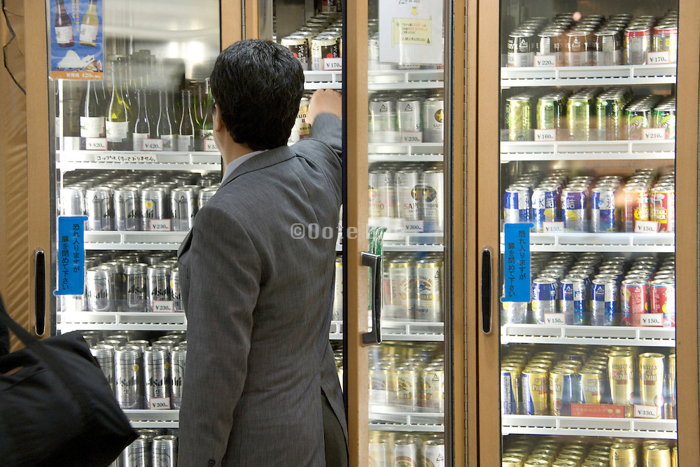Japanese businessman buying a can of beer for on the commute home