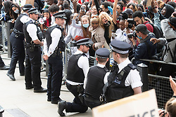 © Licensed to London News Pictures. 03/06/2020. London, UK. Two policemen on duty outside Downing St kneel in front of protesters taking part in a demonstration organised by group Black Lives Matter for the American George Floyd. He who died whilst being arrested by US policemen Derek Chauvin and has caused civil unrest in some US cities. Photo credit: Ray Tang/LNP