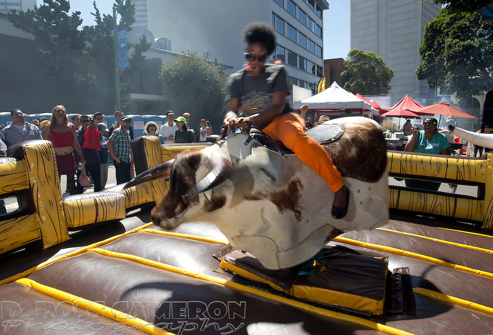 Nina Washington Chantalat of Oakland, Calif. rides a mechanical bull at the annual Pride Festival, Sunday, Aug. 31, 2014 in Oakland. (Photo by D. Ross Cameron)