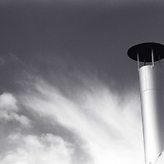 Industrial roof vent-stack against dark sky with white clouds.