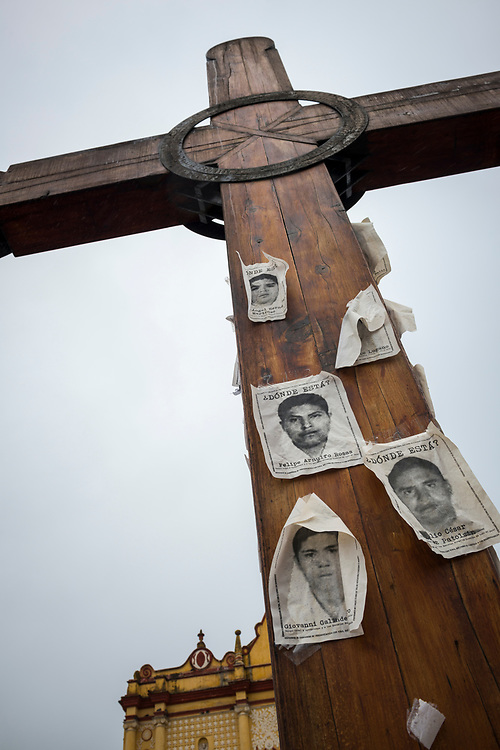 Photos of missing students are nailed to a cross outside the cathedral in San Cristobal de las Casas, in the Mexican state of Chiapas. The photos are of some of the 43 male students who went missing on September 26, 2014 in Iguala, Guerrero, Mexico.