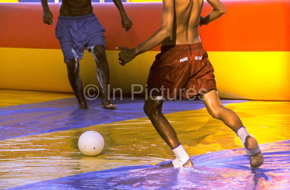 """Playing """"soapy football"""" on an inflatable pitch, Recife, Brazil."""