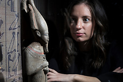 An exhibition at the National Museum of Scotland tells the story of one ancient Egyptian tomb across 1,000 years of use. Built around 1290 BC, the tomb was reused a number of times before being sealed in the 1st Century AD and left undisturbed until its excavation in the 19th Century<br /> <br /> Pictured: Statue of Osiris viewed by Alice Wylie of NMS Press Office