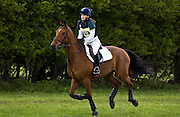 Young woman rides Cleveland Bay cross Thoroughbred bay horse in cross-country section at eventing competition, United Kingdom
