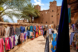 Tourists shopping in Aït Benhaddou, Morocco. Aït Benhaddou is an ighrem (fortified village), situated along the former caravan route between the Sahara and Marrakech in present-day Morocco. There are four families still living in the ancient village. Inside the walls of the ksar are half a dozen (Kasbahs) or merchants houses and other individual dwellings, and is a great example of Moroccan earthen clay architecture.<br /> <br /> Aït Benhaddou has been a UNESCO World Heritage Site since 1987.<br /> <br /> (c) Andrew Wilson | Edinburgh Elite media