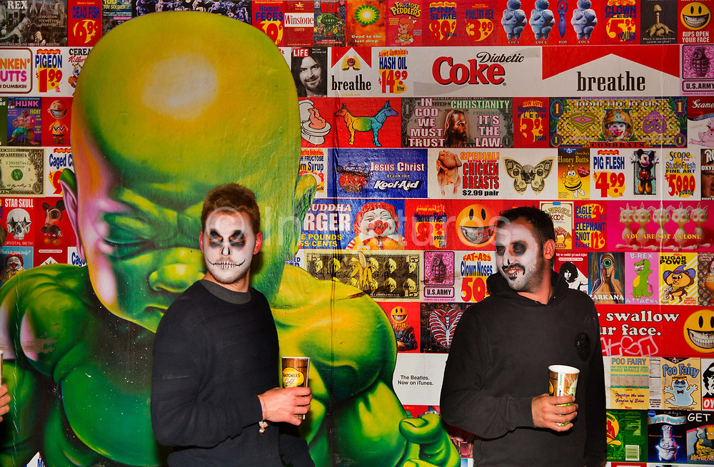 Glastonbury Festival, 2015. Shangri La is a festival of contemporary performing arts held each year within Glastonbury Festival. The theme for the 2015 Shangri La was Protest.  Two men with zombie face paint pass the graphic art of the Shangri La field.