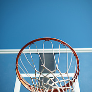 An orange basketball hoop with a transparent backboard with net against a clear blue sky.