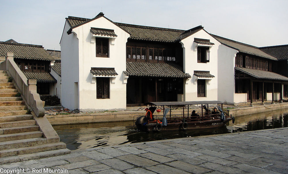 A river boat makes it's way past traditional architecture in Xitang, China.