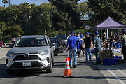 Motorists arrive to the Los Angeles Dodgers Foundation 16th annual Thanksgiving Turkey Giveaway at Dodger Stadium, Thursday, Nov. 19, 2020, in Los Angeles.