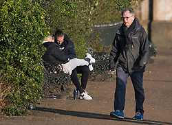 © Licensed to London News Pictures. 04/04/2020. London, UK. A man walks past a couple sat together on a park bench in Hyde Park, London, during a pandemic outbreak of the Coronavirus COVID-19 disease. The public have been told they can only leave their homes when absolutely essential, in an attempt to fight the spread of coronavirus COVID-19 disease. Photo credit: Ben Cawthra/LNP