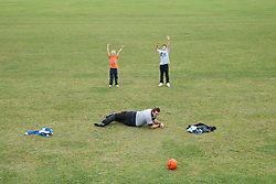 Man and boys playing football, the boys have scored a goal.