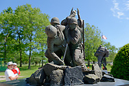 East Meadow, New York, USA. May 25, 2019. A father and young son look at the small metal sculture of six Marines raising a U.S. flag atop Mount Suribachi at Iwo Jima, at the Nassau County Veterans Memorial Plaza on Memorial Day Weekend at Eisenhower Park on Long Island. The sculpture was originally the model for a life-sized one.