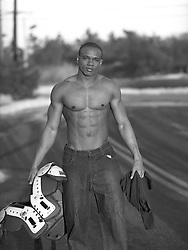 good looking African American Man without a shirt walking in the street