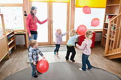 Female educator and four kids playing with red balloons in kindergarten