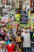 People some of them wearing face masks, hold placards and banners as they attend a march against 'ecocide' seeking to step up pressure on Shell and demand an end on fossil fuel extraction. Earlier on Tuesday, Sept 8, 2020 - Extinction Rebellion activists staged a performative protest enacting a crime scene outside Shell Headquarters in Jubilee Gardens, central London. Environmental nonviolent activists group Extinction Rebellion enters its 8th day of continuous ten days protests to disrupt political institutions throughout peaceful actions swarming central London into a standoff, demanding that central government obeys and delivers Climate Emergency bill. (VXP Photo/ Vudi Xhymshiti)