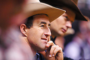 """15 DECEMBER 2002 - LAS VEGAS, NV, USA: Saddle bronc rider Scott Johnston, left, from Gustine, TX, and  bareback rider Darren Clarke watch the steer wrestling competition in the 10th round of the National Finals Rodeo in the Thomas and Mack Center in Las Vegas, NV, December 15, 2002. The NFR is the """"Super Bowl"""" of rodeo. Only the top 15 cowboys from each event are invited to participate in the NFR, which runs for 10 days every December. All ten performances of the NFR sell out every year. PHOTO BY JACK KURTZ"""