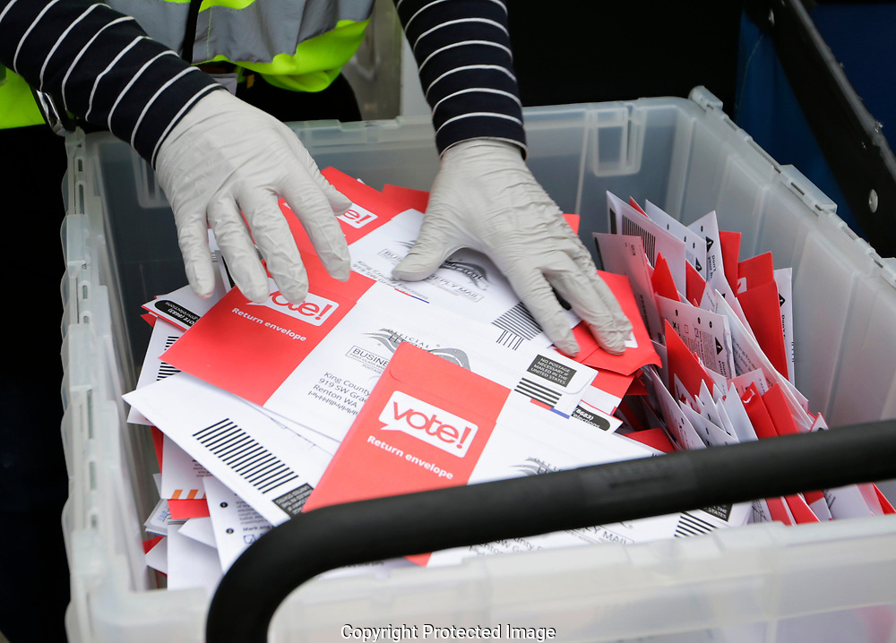 Wearing gloves, a King County Election worker collect ballots from a drop box in the Washington State primary, Tuesday, March 10, 2020, in Seattle. Washington is a vote by mail state. (AP Photo/John Froschauer)