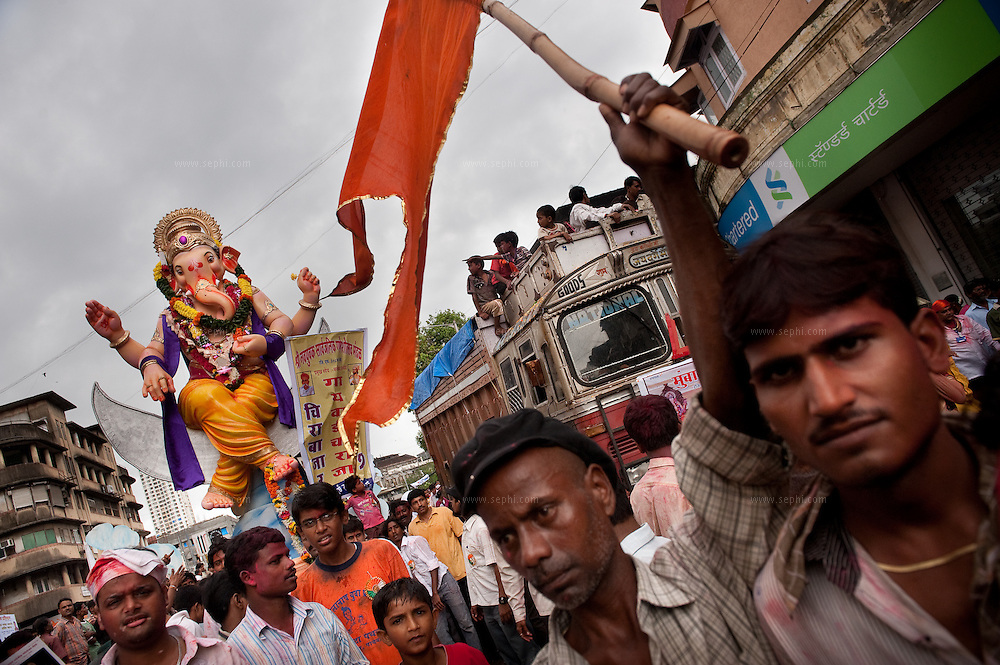 An idol of lord Ganesh being paraded on the streets of Mumbai on the way for immersion in the Indian ocean on the last day of the Ganesh Chaturthi festival. Ganesh, the elephant-headed son of Shiva and Parvati is widely worshiped as the supreme God of wisdom, prosperity and good fortune. Mumbai, September 2009.