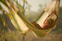 Young woman relaxing in hammock in Mexico.