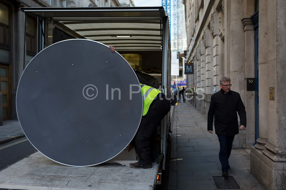 A workman offloads round dinner special event tables to a company in the City of London - aka the Square Mile - the capitals financial district, on 17th January 2019, in London, England.