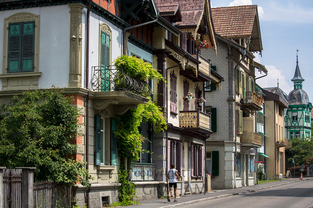 Jogger passes traditional houses in Neugasse at Interlaken in the Bernese Oberland, Switzerland