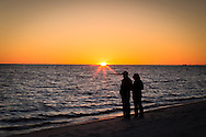 A couple in silhouette on the beach at sunset