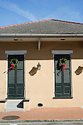 Christmas wreaths hang on green shutters on a house in the French District in New Orleans, Louisiana.