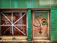 A closed storefront with a green facade and a large girls face painted on the door.