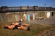 Before the area was completely redeveloped with a pleasure fairground, 1990s sunbathers stretch out on bare grass on the seafront that still shows its heyday landscape, on 2nd August 1993, at Southend-on-Sea, Essex, England.