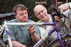 Father and adult son with Downs Syndrome mending bicycle,
