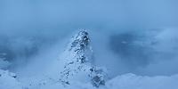 Hiker on summit of Volandstind during clearing winter storm, Flakdstadøy, Lofoten Islands, Norway