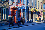Quebec City, Quebec, Canada -- November 30, 2019.  Holiday shoppers and tourists walk past shops and a boutique hotel on a side street in Quebec City, Canada.