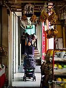 13 DECEMBER 2018 - SINGAPORE:  A woman pushes a baby carriage under the porticos in the shophouses of the Geylang neighborhood. The Geylang area of Singapore, between the Central Business District and Changi Airport, was originally coconut plantations and Malay villages. During Singapore's boom the coconut plantations and other farms were pushed out and now the area is a working class community of Malay, Indian and Chinese people. In the 2000s, developers started gentrifying Geylang and new housing estate developments were built.     PHOTO BY JACK KURTZ