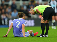 NEWCASTLE UPON TYNE, ENGLAND - SEPTEMBER 17: the referee, Mike Dean, checks on the injured Luke Ayling of Leeds United during the Premier League match between Newcastle United and Leeds United at St. James Park on September 17, 2021 in Newcastle upon Tyne, England. (Photo by MB Media)