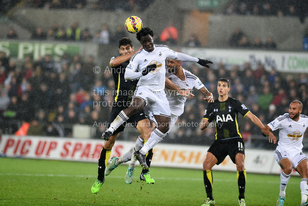 Wilfried Bony of Swansea city wins a header.  Barclays Premier League match, Swansea city v Tottenham Hotspur at the Liberty Stadium in Swansea, South Wales on Sunday 14th December 2014<br /> pic by Andrew Orchard, Andrew Orchard sports photography.