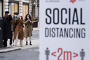 Group of young women take selfies and pictures of one another near to a social distancing sign on regent Street as the national coronavirus lockdown three continues on 5th March 2021 in London, United Kingdom. With the roadmap for coming out of the lockdown has been laid out, this nationwide lockdown continues to advise all citizens to follow the message to stay at home, protect the NHS and save lives, and the streets of the capital are quiet and empty of normal numbers of people.