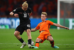 AMSTERDAM, NETHERLANDS - JUNE 17: Xaver Schlager of Austria is challenged by Frenkie de Jong of Netherlands during the UEFA Euro 2020 Championship Group C match between the Netherlands and Austria at Johan Cruijff Arena on June 17, 2021 in Amsterdam, Netherlands. (Photo by Christopher Lee - UEFA)