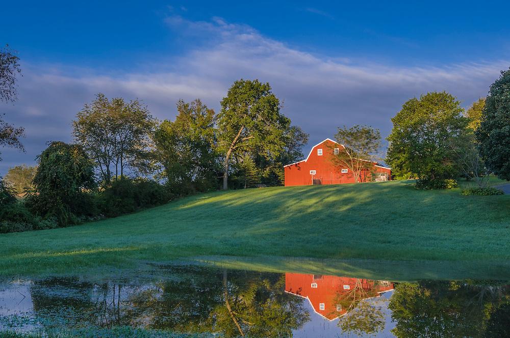 Red barn on summer hillside reflected in little pond, Woodstock, CT