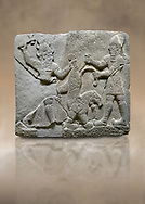 Hittite relief sculpted orthostat stone panel of Herald's Wall Basalt, Karkamıs, (Kargamıs), Carchemish (Karkemish), 900-700 B.C. Anatolian Civilisations Museum, Ankara, Turkey.<br /> <br /> On the right is a bearded human figure with a short skirt; with the dagger in his right hand, he is stabbing the lion standing on his front legs while holding the lion's tail with his left hand. On the left is a bearded god figure with a horned-headdress, who grasps the lion's hind leg while holding the ax over his head with his right hand. <br /> <br /> Against a brown art background. .<br />  <br /> If you prefer to buy from our ALAMY STOCK LIBRARY page at https://www.alamy.com/portfolio/paul-williams-funkystock/hittite-art-antiquities.html  - Type  Karkamıs in LOWER SEARCH WITHIN GALLERY box. Refine search by adding background colour, place, museum etc.<br /> <br /> Visit our HITTITE PHOTO COLLECTIONS for more photos to download or buy as wall art prints https://funkystock.photoshelter.com/gallery-collection/The-Hittites-Art-Artefacts-Antiquities-Historic-Sites-Pictures-Images-of/C0000NUBSMhSc3Oo